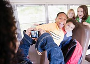 Girl taking photographs on school bus