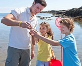 Father with daughter and son looking at small crab on sunny beach