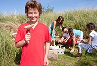 Portrait of smiling boy holding hotdog on fork with family and barbecue in background
