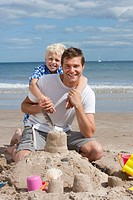 Portrait of smiling father and son hugging in front of sandcastle on sunny beach