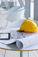 Digital tablet, blueprint, hard hat and eyeglasses on table