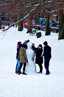 Making a snowman at Parkers Piece in winter, Cambridge, England