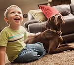 Caucasian boy sitting on floor with dog