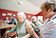 Influenza vaccination being injected by a nurse into a patient´s upper arm in a residential care home. This vaccine is for the northern hemisphere in ...