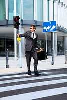young caucasian businessman in park walking on red light on zebra crossing