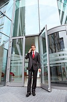 young caucasian businessman at office exterior talking on cellphone