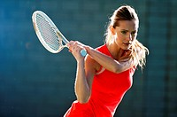 A female tennis player hitting the ball backhand