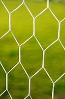 Detail of a soccer football goal net and the grass field behind it