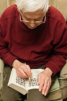 A senior elderly man in his 80's doing a crossword puzzle at home in England , Britain , Uk