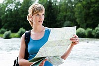 Germany, Bavaria, Mid adult woman with map near Isar river, smiling