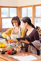Hispanic friends cooking together in kitchen with digital tablet
