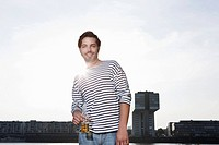 Germany, Cologne, Young man with beer bottle, smiling, portrait