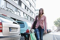 Germany, Cologne, Young woman with shopping bags, smiling, portrait