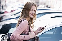 Germany, Cologne, Young woman with phone near parking lot, smiling, portrait (thumbnail)