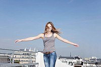 Germany, Cologne, Young woman at parking building, smiling, portrait