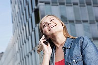 Germany, Cologne, Young woman on phone, smiling, portrait