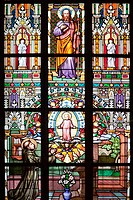 Part of a Stained Glass Window depicting St Thomas standing in the center, holding a book and a Spear, flanked by two Winged Angel figures and a multi...
