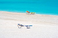 A couple of beach chairs in a deserted beach