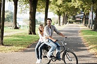 Germany, Cologne, Young couple on bicycle, smiling, portrait