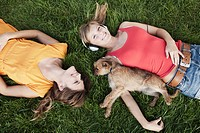 Germany, Cologne, Young woman lying in grass with dog, smiling