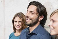 Germany, Cologne, Young man and woman leaning on wall, smiling