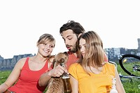 Germany, Cologne, Young man and woman with dog and beer bottle in grass, smiling