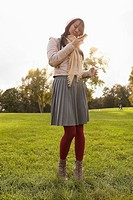 Germany, Cologne, Young woman with cell phone in park
