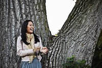 Germany, Cologne, Young woman near tree trunk in park, smiling