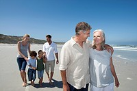 Mature couple on beach with family