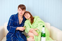 Young pair at home on sofa with sparkling wine