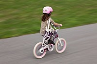 Young girl in motion on child´s bicycle