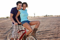 Couple on bicycle in desert landscape