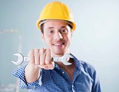 Young man wearing hard hat holding wrench, portrait