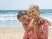 Grandmother and granddaughter hugging on beach