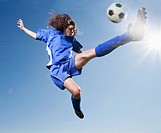 Caucasian woman kicking soccer ball
