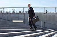 Germany, Bavaria, Munich, Businessman walking on stairs with briefcase, smiling