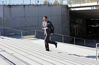Germany, Bavaria, Munich, Businessman walking on stairs with briefcase