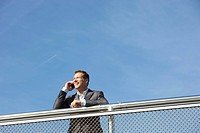 Germany, Bavaria, Munich, Businessman talking on cell phone, smiling