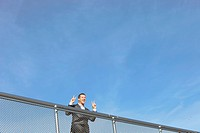 Germany, Bavaria, Munich, Businessman standing near railings, smiling