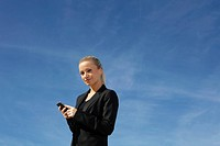 Germany, Bavaria, Munich, Businesswoman with cell phone, smiling, portrait