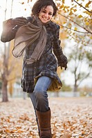 Caucasian woman running in autumn leaves