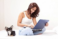 Young woman using laptop with dog on bed, smiling
