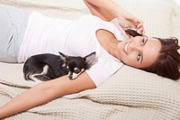 Young woman on phone with chihuahua, smiling