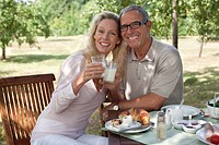 Smiling mature couple outdoors at breakfast table