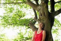 Germany, Bavaria, Mid adult woman leaning on tree, smiling