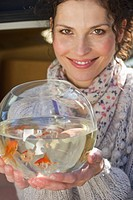 Germany, Bavaria, Grobenzell, Mid adult woman holding goldfish bowl, smiling, portrait