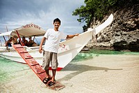 Man with tour boat on tropical beach