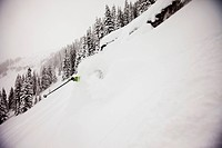 A athletic skier rips fresh deep powder turns in the backcountry on a stormy day in Colorado.