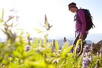 A woman taking an early morning hike through some flowers.