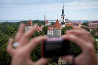 Hands hold compact camera to capture overhead of city with churches and towers from Toompea hill, Tallinn, Harjumaa, Estonia